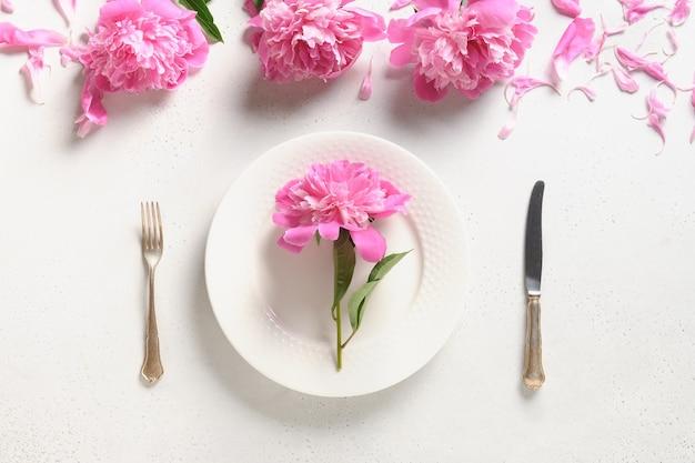 Configuração de mesa festiva com flores de peônia rosa em uma mesa branca vista de cima