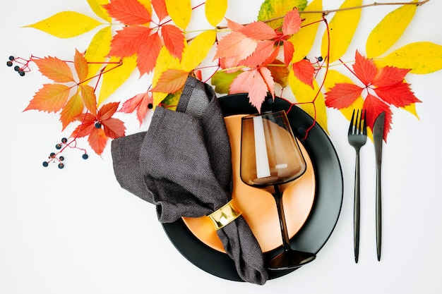 Configuração de mesa festiva com folhas de outono brilhantes em fundo branco. camada plana, vista superior