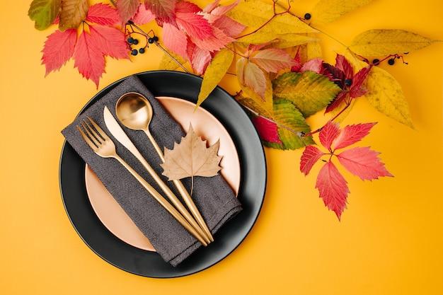 Configuração de mesa festiva com folhas de outono brilhantes em fundo laranja. camada plana, vista superior, espaço de cópia