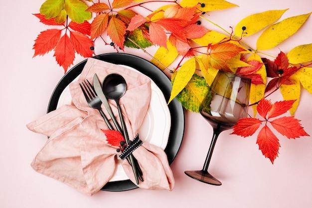 Configuração de mesa festiva com folhas de outono brilhantes em fundo pastel. camada plana, vista superior, espaço de cópia