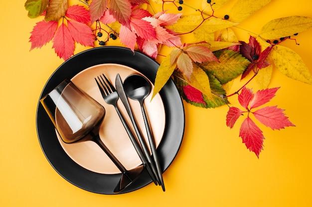 Configuração de mesa festiva com pratos pretos e taça de vinho e folhas de outono brilhantes em laranja