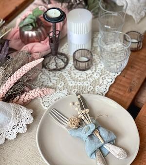 Configuração de mesa festiva com ramos de flores secas e elementos decorativos.