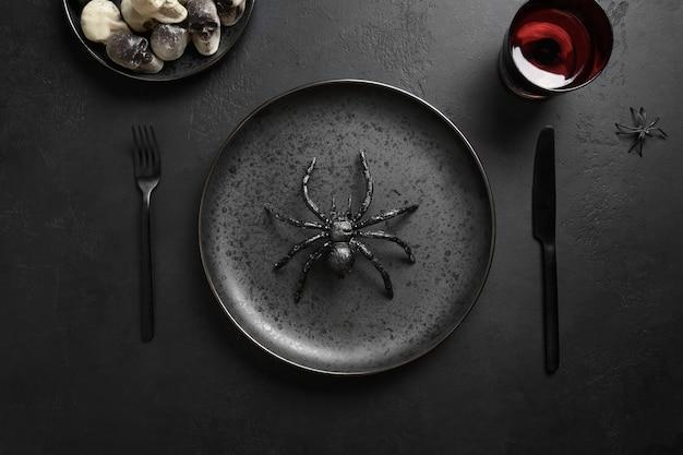 Configuração de mesa festiva de halloween com aranha e decoração preta