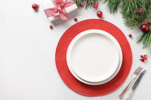 Configuração de mesa festiva de natal com decorações elegantes de férias brancas e vermelhas em branco.
