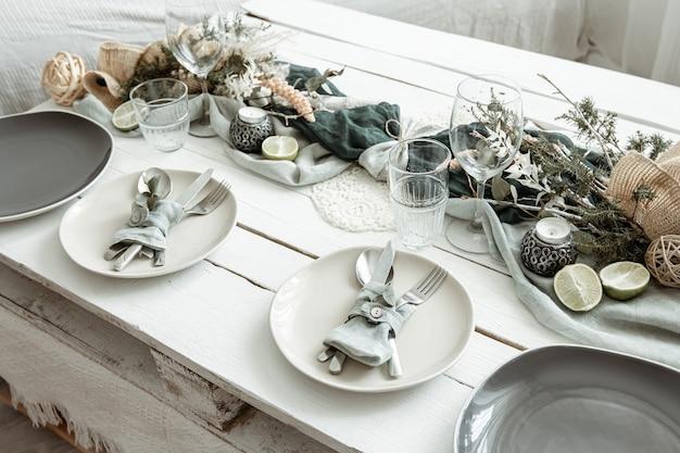 Configuração de mesa festiva elegante com detalhes de decoração escandinava em uma superfície de madeira.