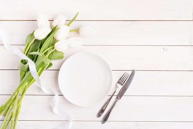 Configuração de mesa festiva em placa branca, placa branca e vista superior de tulipas em fundo de madeira