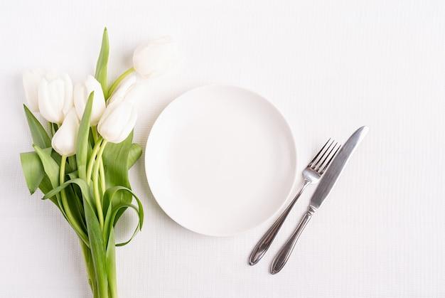 Configuração de mesa festiva em placa branca, placa branca e vista superior de tulipas no fundo