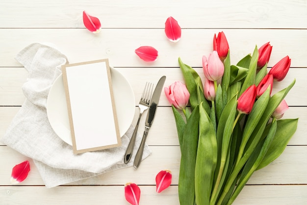 Configuração de mesa festiva romântica com talheres de prata e buquê de tulipas rosa frescas.