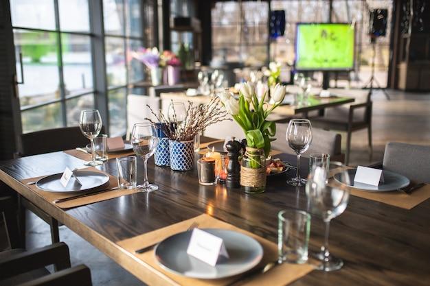 Configuração de mesa no restaurante. copos, pratos e talheres