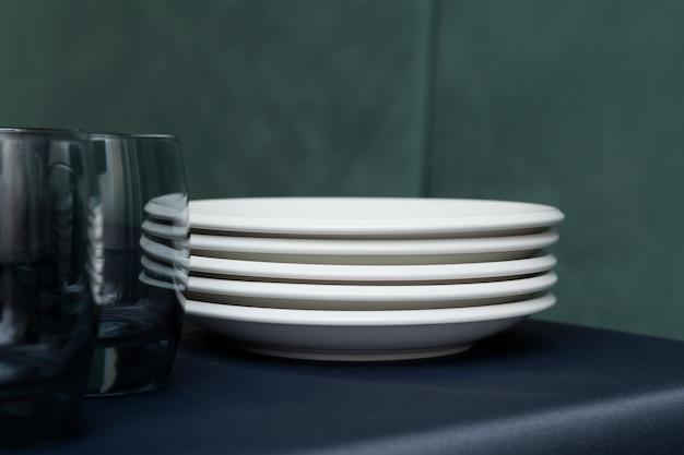 Configuração de mesa para férias. pratos brancos e óculos escuros na beira da mesa cinza.