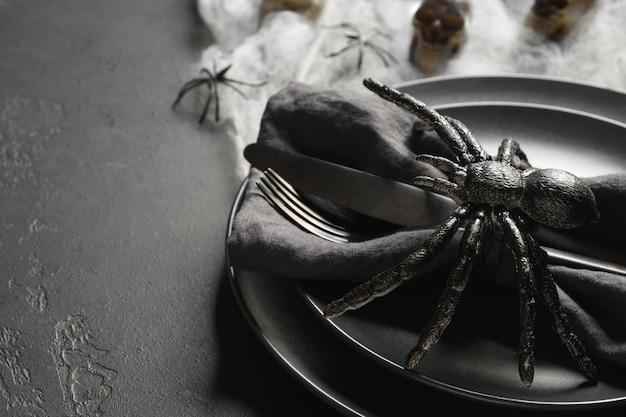 Configuração de mesa preta de halloween com aranha, caveira e teia na mesa preta escura