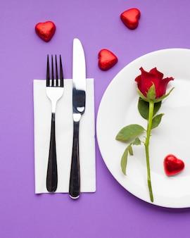 Configuração de mesa romântica plana leiga com rosa vermelha