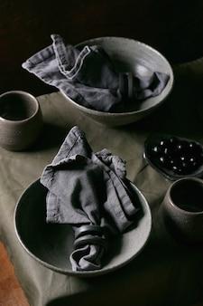 Configuração de mesa rústica com talheres de cerâmica artesanais vazios, tigelas cinzas ásperas e xícaras na toalha de mesa de linho. fundo escuro