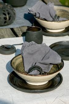 Configuração de mesa rústica do lado de fora no jardim com talheres de cerâmica artesanais vazios, pratos pretos e tigelas ásperas, decorações de abóbora, na toalha de mesa de linho sobre a velha mesa de madeira. festa de jardim. fechar-se