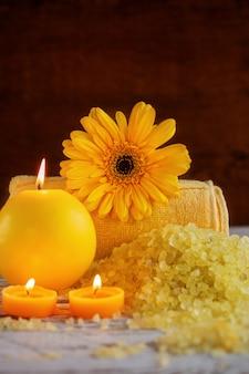 Configuração de produtos amarelo spa. sal marinho, toalha e velas no fundo escuro de madeira
