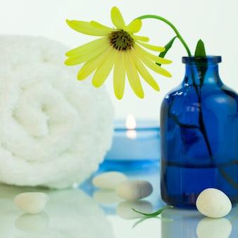 Configuração de spa com linda margarida amarela, seixos, toalha e vela