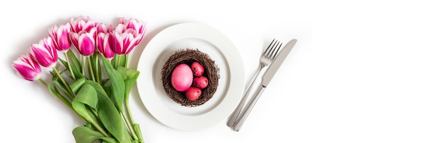 Configuração de tabela do feriado da páscoa com ovos-de-rosa em um ninho e flores de tulipa em um fundo branco. bandeira. copie o espaço, vista superior.