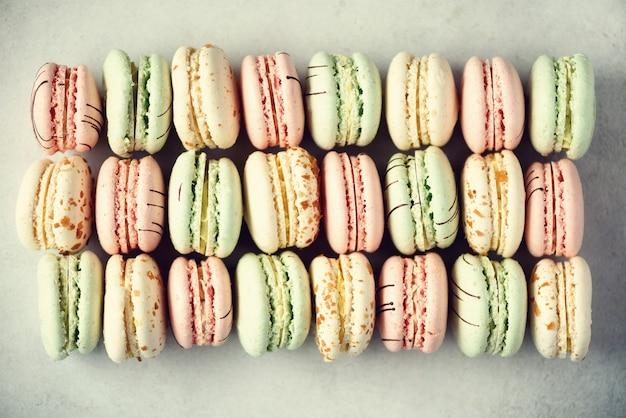 Configuração lisa do bolinho de amêndoa francês colorido. as cores pastel picam macarons cor-de-rosa, verdes, amarelos. feriados e celebrações conceito. presente doce para mulher, menina