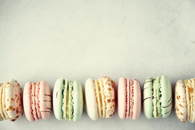Configuração lisa do bolinho de amêndoa francês colorido. pastel cores rosa, verde, amarelo macarons