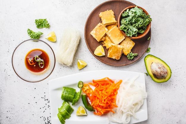 Configuração lisa do macarronete de arroz vietnamiano dos ingredientes com tofu e os vegetais grelhados. conceito de comida vegan.