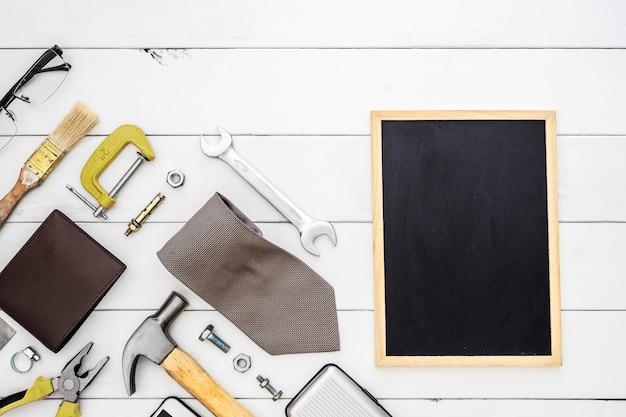 Configuração lisa do quadro-negro do espaço vazio com as ferramentas acessíveis do colarinho azul da construção e os acessórios dos homens sobre o fundo de madeira.