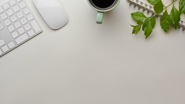 Configuração plana criativa da área de trabalho com teclado de computador, mouse, xícara e folhas na mesa com espaço de cópia