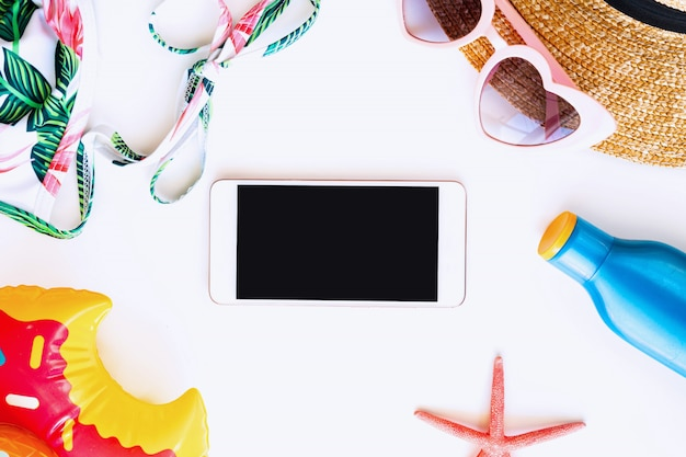 Configuração plana de acessórios de verão e smartphone de tela em branco para cópia espaço isolado, vista superior. conceito de férias tropicais.