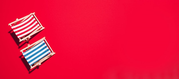 Configuração plana de espreguiçadeiras de praia sobre fundo vermelho, com espaço de cópia.