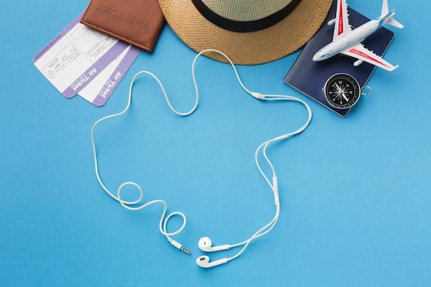 Configuração plana de itens essenciais de viagem com fones de ouvido e bússola