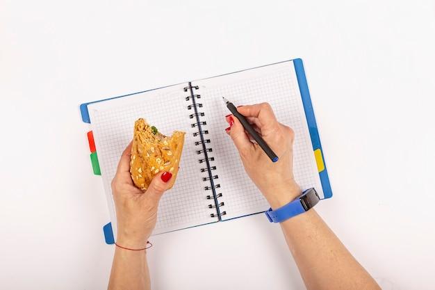 Configuração plana de material escolar em um espaço azul minimalista. mulher come sanduíche. lanche saudável no local de trabalho do escritório.