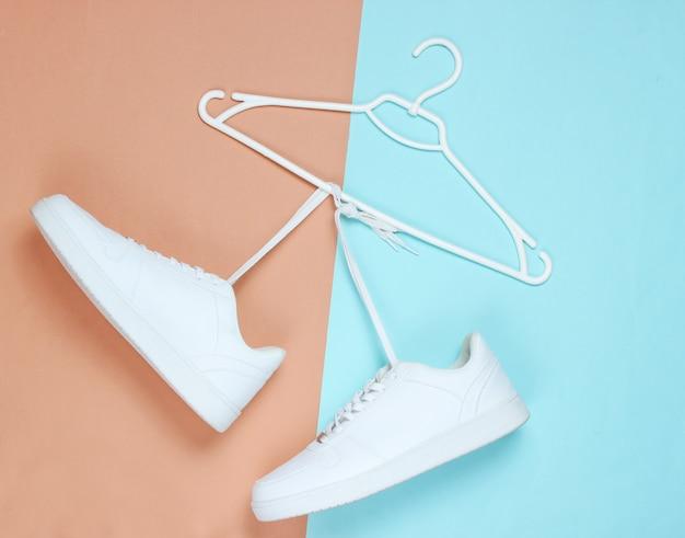 Configuração plana de sapatos de tênis branco moderno com cabide em fundo pastel.