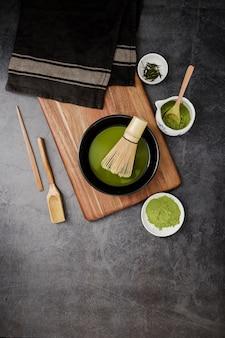 Configuração plana de toalhas e itens essenciais de chá matcha