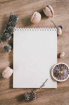 Configuração plana do caderno marrom em branco na mesa de madeira.