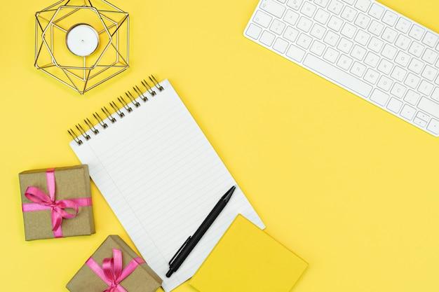 Configuração plana do espaço de trabalho amarelo brilhante com livro de nota do teclado e caixas de presente com fita rosa, fundo amarelo