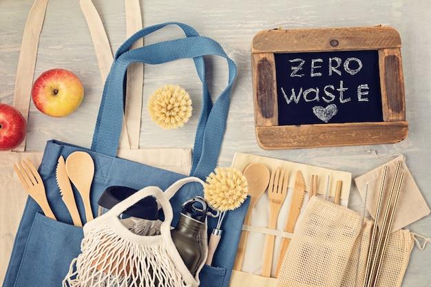 Configuração plana do kit zero waste. conjunto de talheres de bambu ecológicos, saco de malha de algodão, copo de café reutilizável, escovas e garrafa de água. estilo de vida sustentável, ético e sem plástico. vista do topo