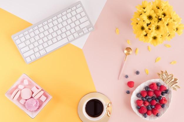 Configuração plana e vista de cima da mesa de escritório de trabalho com teclado labtop, flores e bagas em fundo rosa e amarelo. layout da mesa pastel feminina de verão
