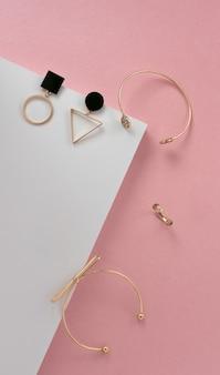 Configuração plana vertical de acessórios modernos menina dourada na superfície do canto rosa e branco