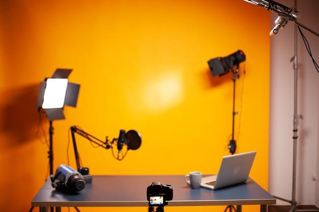 Configuração profissional de podcast e vlogging no estúdio com parede amarela