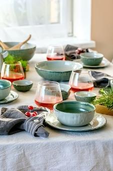 Configuração rústica de mesa de natal com talheres de cerâmica artesanais vazios, pratos e tigelas, decorações de anjo de natal, copos de suco vermelho, galhos verdes e frutas na toalha de mesa branca em frente à janela