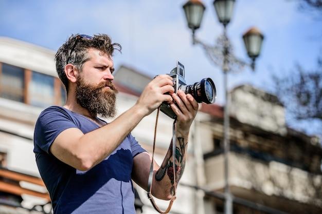 Configurações manuais. fotógrafo segura câmera vintage. blogger moderno. criador de conteúdo. fotógrafo de hipster barbudo de homem. fotógrafo com barba e bigode. homem com barba comprida tirando fotos.