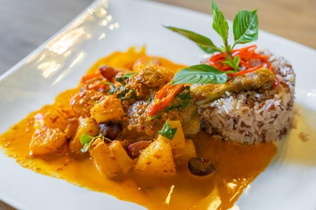 Confit de pato com curry vermelho servido com arroz integral no prato