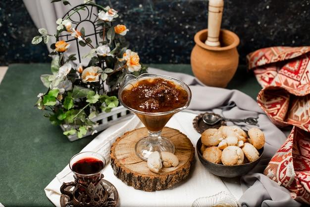Confiture, biscoitos de manteiga e um copo de chá