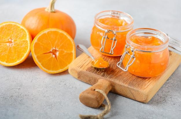 Confiture caseiro da abóbora e da laranja no uns frascos.