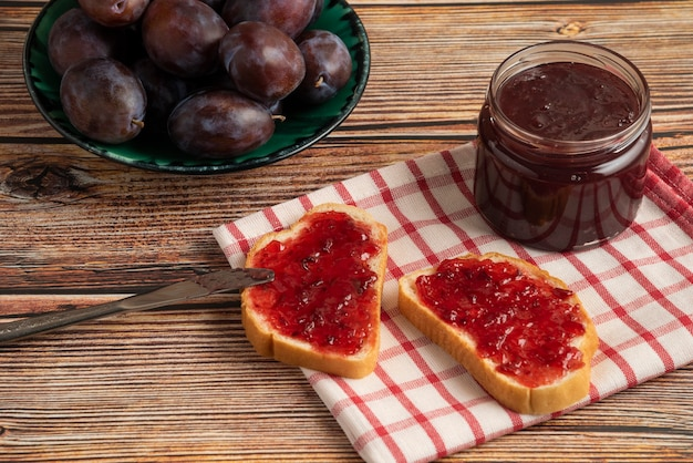 Confiture de ameixa em pães torrados e frutas em uma toalha xadrez.