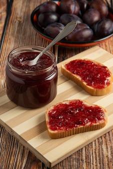 Confiture de ameixas em potes de vidro com tostas de pão.