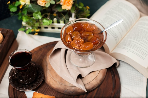 Confiture de figo e um copo de chá preto.