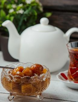 Confiture de frutas amarelas com um copo de chá preto.