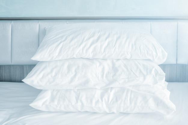 Confortáveis almofadas macias empilham nas folhas de cama brancas
