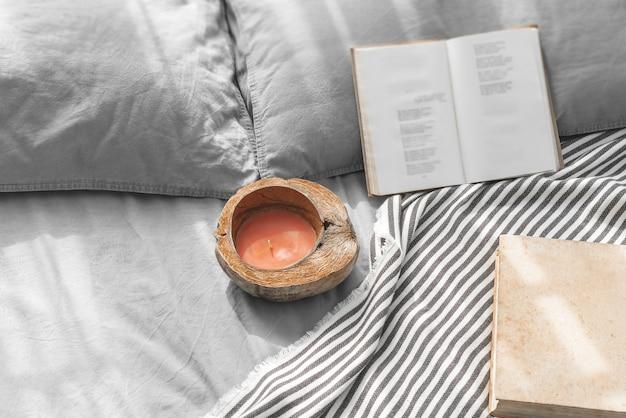 Confortável cama bagunçada com dois travesseiros, roupa de cama cinza com livros e vela com casca de coco.
