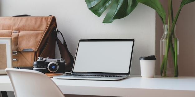 Confortável espaço de trabalho com computador portátil de tela em branco com mala postal